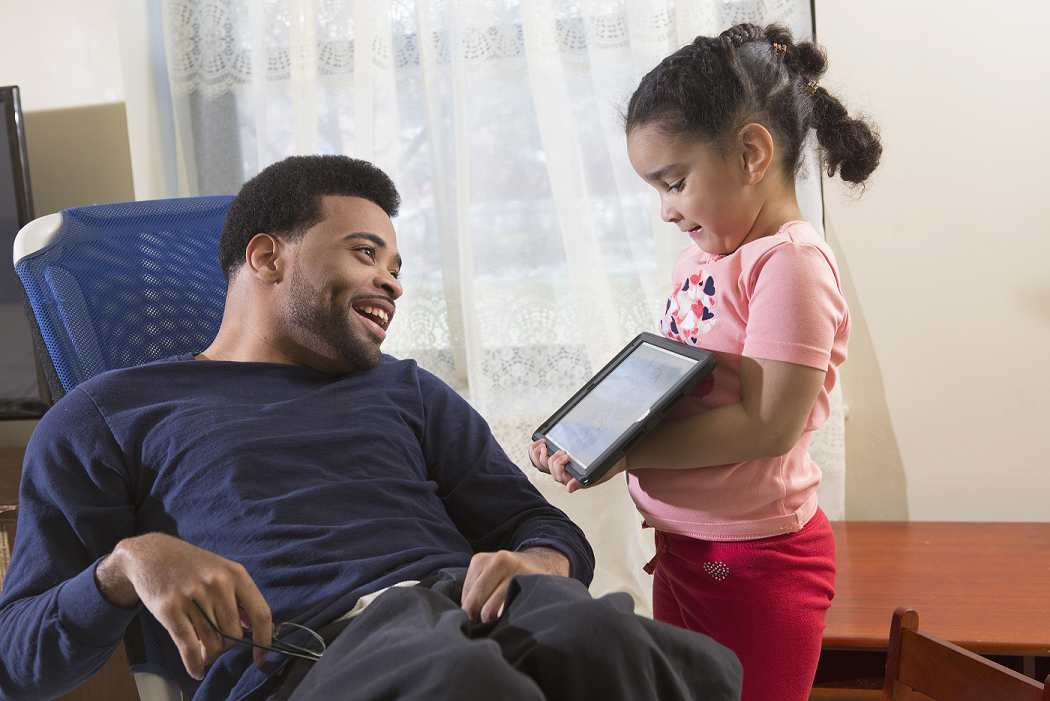 Father with young daughter smiling while using a tablet