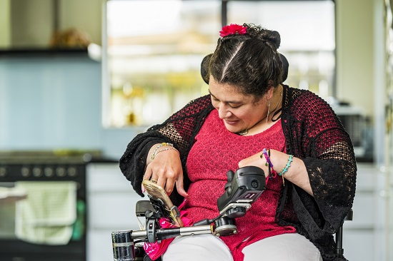 Woman with cerebral palsy using her cell phone. She is wearing a red top and black shawl and has a red flower in her hair.