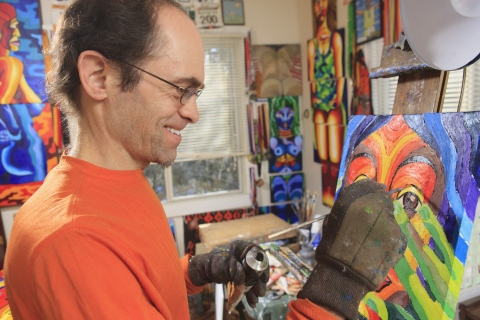 Artist with autism wearing an orange shirt and glasses, standing in his art studio painting a colorful image of a persons face.