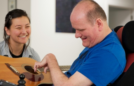 Older man and his attendant smiling as he strums a guitar.