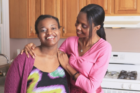 Two sisters, one with her arm around the other, standing in the kitchen, smiling.