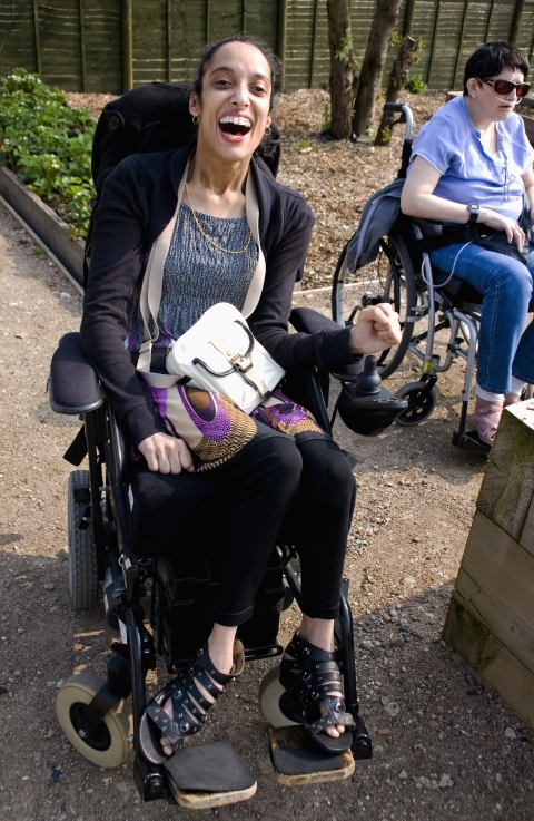 Young woman with cerebral palsy, laughing while sitting outside in her wheelchair.