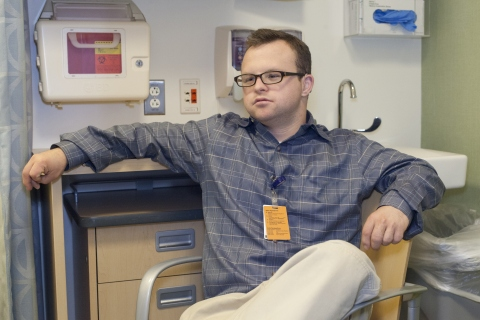 Young man with Down Syndrome wearing glasses, khaki pants, and a blue shirt, sitting in a medical exam room.